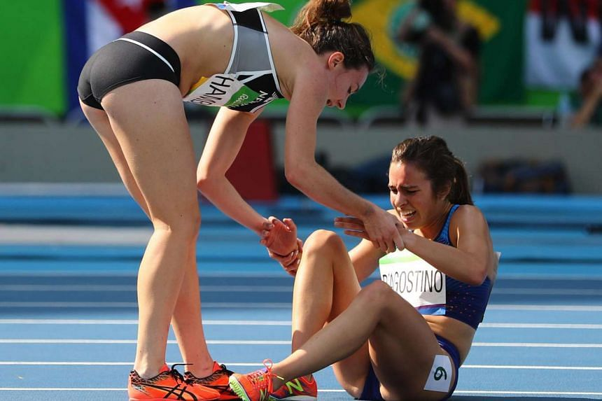 New Zealand's Nikki Hamblin helping Abbey D'Agostino of the US to her feet during their 5,000m heat.