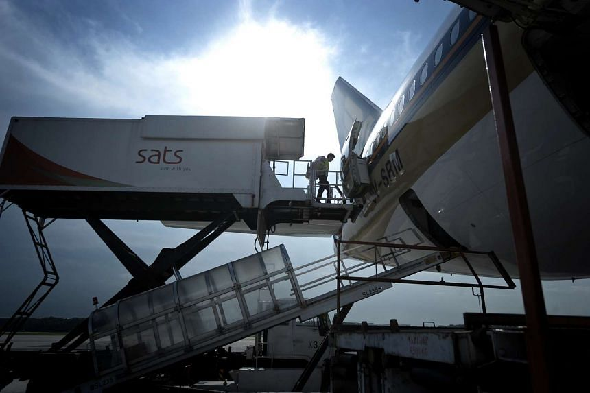A worker from Singapore Airport Terminal Services (Sats) moves out from a elevated inflight catering truck into an aircraft.