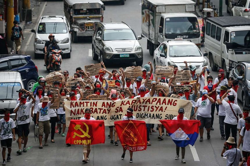 Filipino Communists hold banners and flags as they march along a street during a spontaneous rally for peace talks in Manila, on Aug 20, 2016.