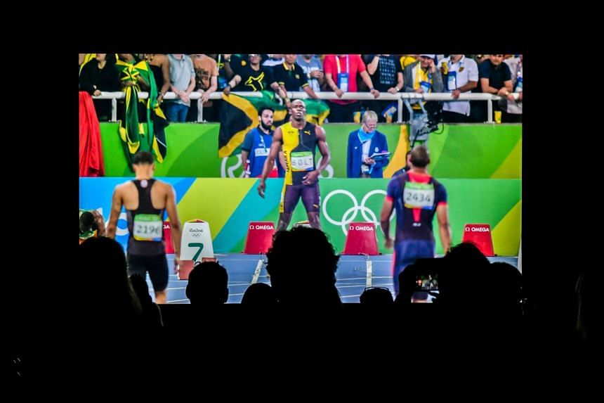 People watch a replay of the 110m race on a ultra high definition 8K screen inside the International Broadcast Center on Aug 15, 2016.