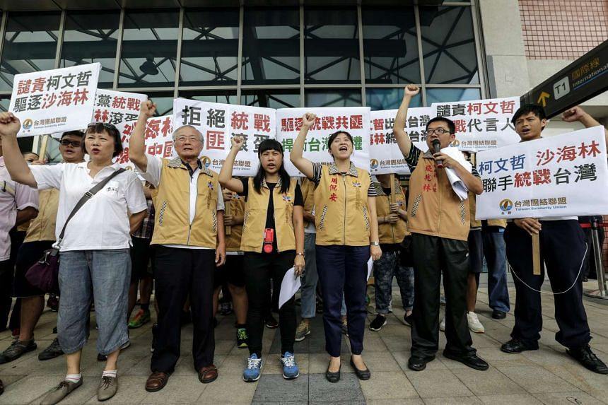 Members of the pro-independence Taiwan Solidarity Union shout anti-China slogans at the Taipei Songshan Airport to protest for the arrival of Shanghai official Sha Hailin, in Taipei on Aug 22, 2016.
