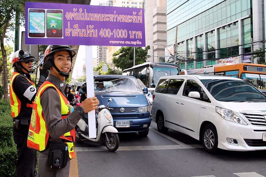 A Thai traffic policeman holds a banner reading 'No Pokemon Go while driving, violators will be fined' during the 'Pokemon Traffic No Go' campaign at a busy street in Bangkok, Thailand, on Aug 22, 2016.