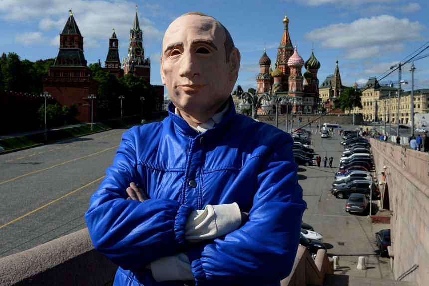 Roman Roslovtsev, wearing a rubber mask depicting President Vladimir Putin, poses for a picture in central Moscow on May 12, 2016.