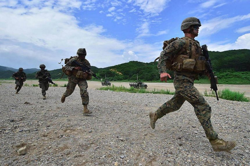 South Korea and US Marines run to a position during a joint military drill at a fire training field in the southeastern port of Pohang on July 6.