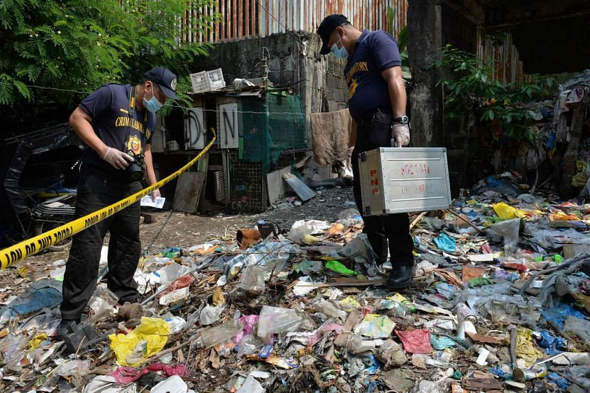 Philippine police forensic investigors look for evidence after members of a suspected drug syndicate were killed after a shootout with police in Manila in July. President Rodrigo Duterte has vowed to wage a bloody war on crime that has human rights a