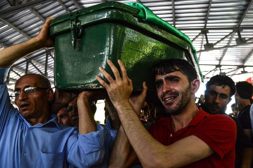 A man cries as he carries a coffin during a funeral for victims of the attack on a wedding party that left 51 dead in southeastern Turkey.