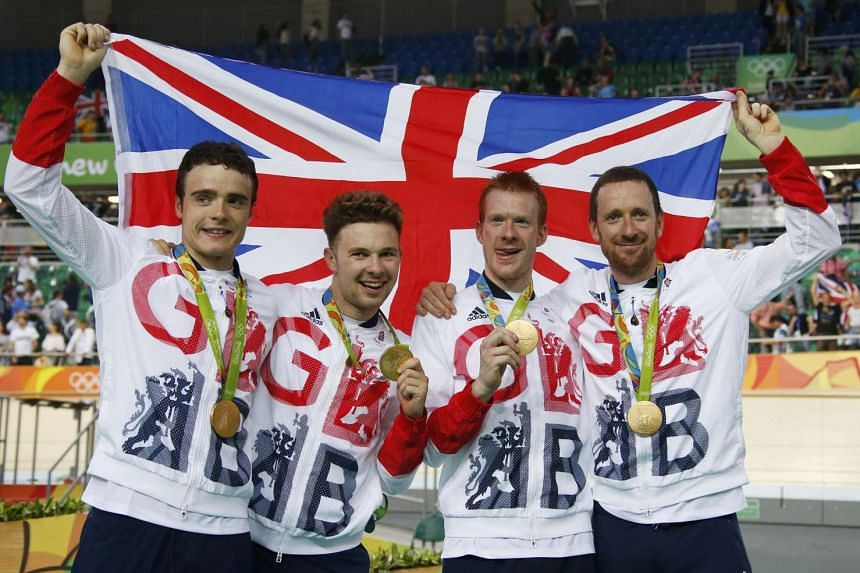 Steven Burke, Owain Doull, Ed Clancy and Bradley Wiggins of Britain pose with the gold medals in cycling and their country's flag.