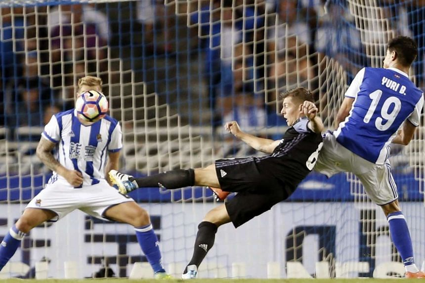 Real Madrid's German midfielder Toni Kroos (centre) shoots at goal next to Real Sociedad's Yuri B.