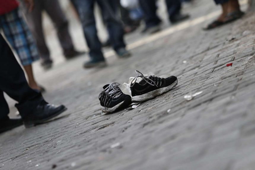 People stand near a pair of shoes said to belong to a victim of the bomb attack on the wedding in Turkey.