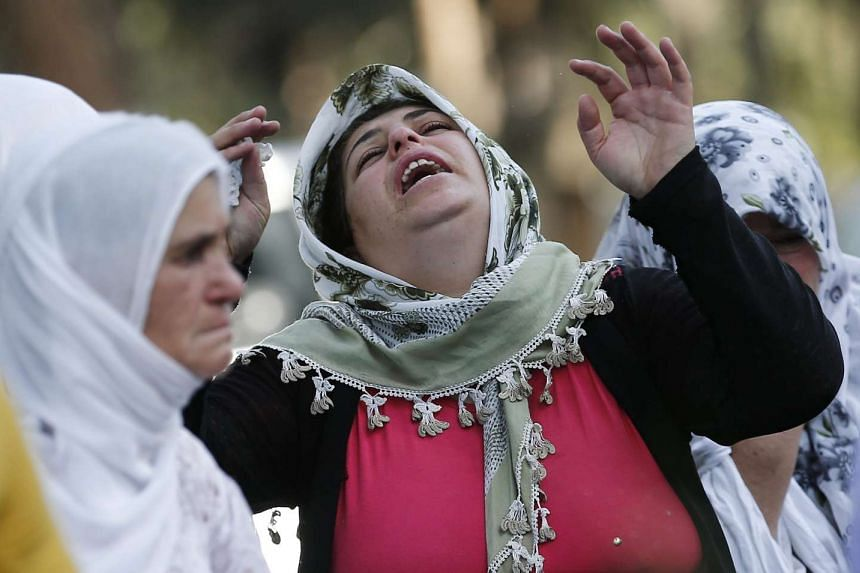 Relatives mourn the victims killed in the bomb attack on the wedding party in Turkey.