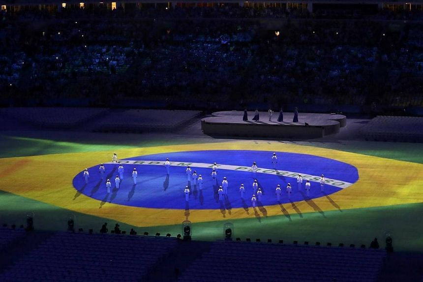 The Brazilian national flag is seen projected on the stage.