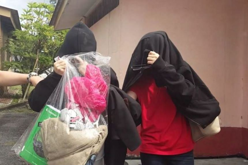 Quek Chin Fern and daughter Cheryl Isabella Lim being escorted out of court in Pekan Nenas Immigration Depot on August 22.