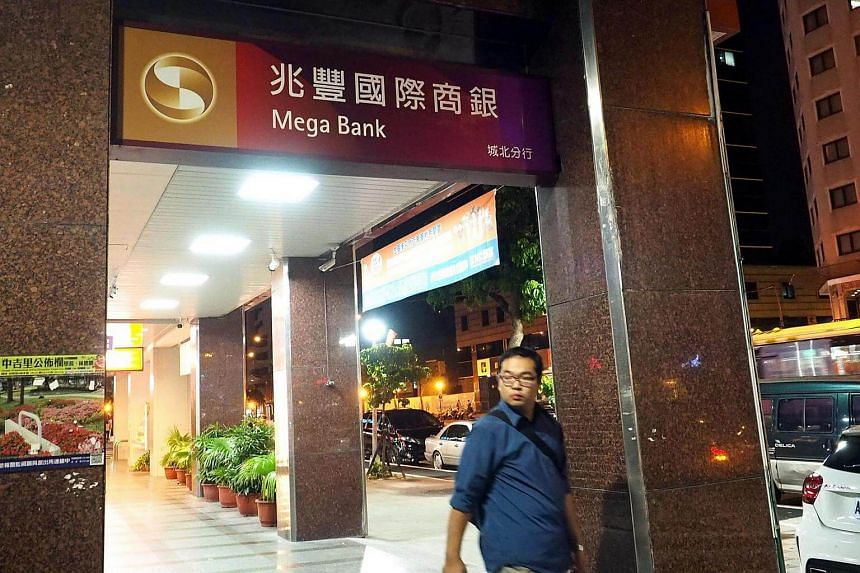 A pedestrian walks past the logo of Mega International Commercial Bank in Taipei, Taiwan, on August 19.