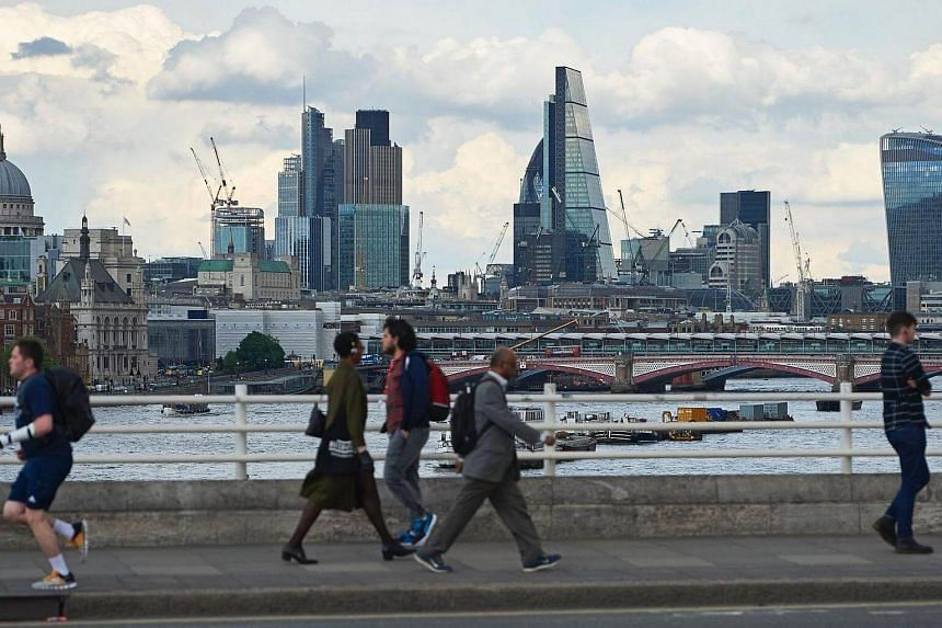 A skyline of buildings in London city as seen from Waterloo Bridge as pedestrians walk by in central London.