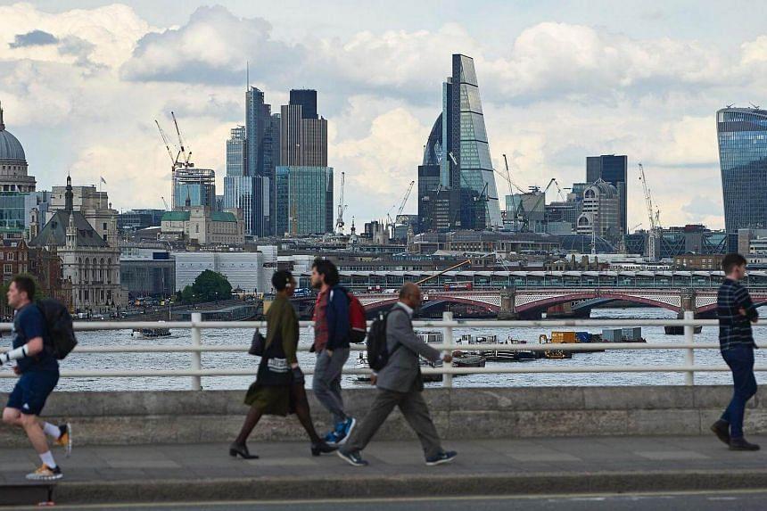 A skyline of buildings in London city as seen from Waterloo Bridge as pedestrians walk by in central London.