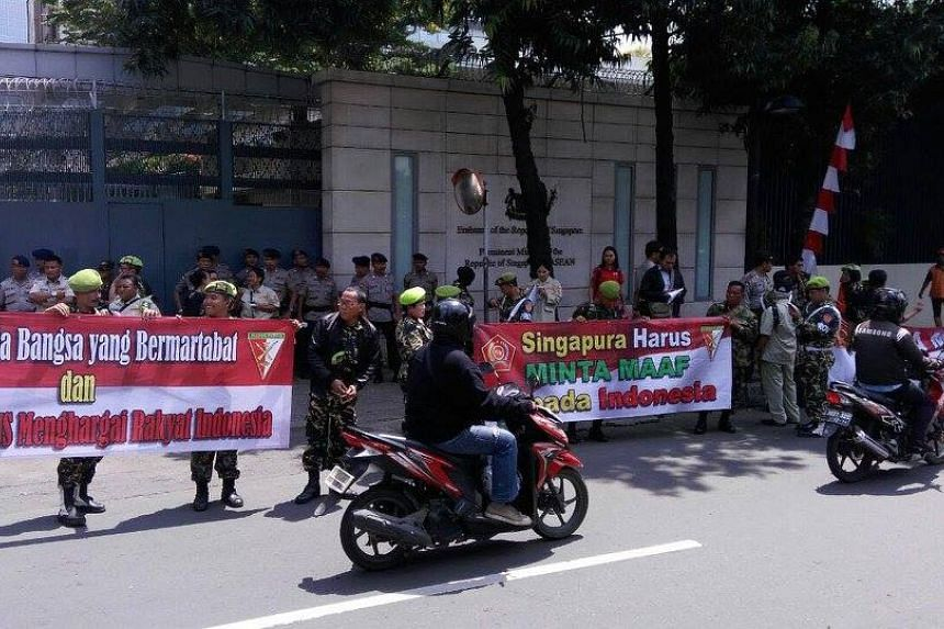 Demonstrators carrying banners outside the Singapore Embassy in Jakarta on Aug 23, 2016.