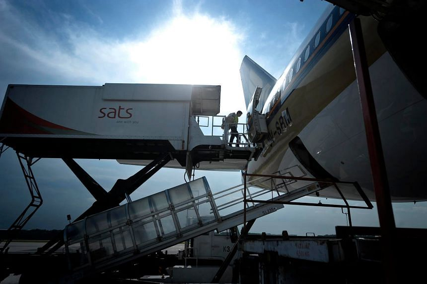 A worker from Sats moves out from an elevated in-flight catering truck into an aircraft.