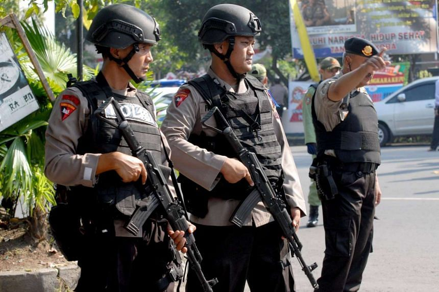 Indonesian police stand guard outside a police station in the Indonesian city of Solo on July 5.