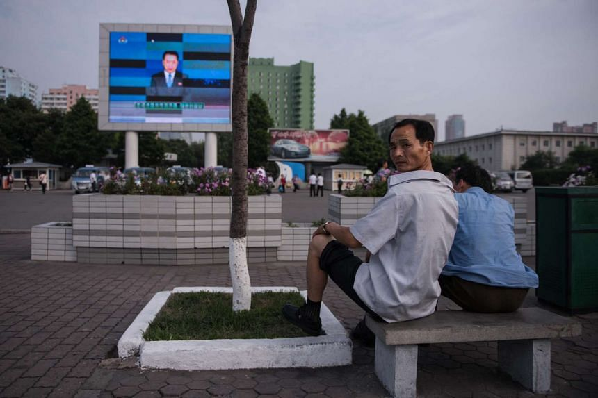 In a photo taken on July 11, 2016, a man watches a news broadcast on a giant screen in Pyongyang, North Korea.