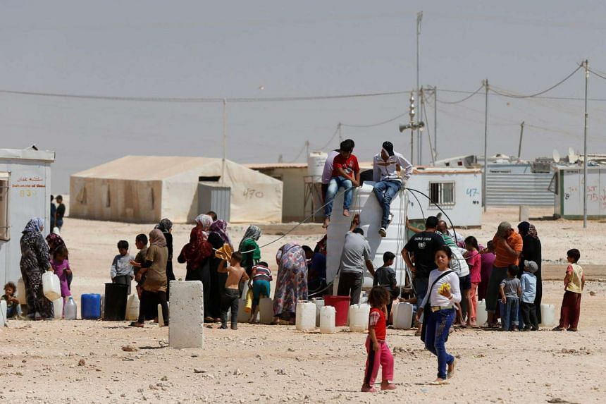 Syrian refugees collect water at the Al-Zaatari refugee camp in Mafraq, Jordan, near the border with Syria.