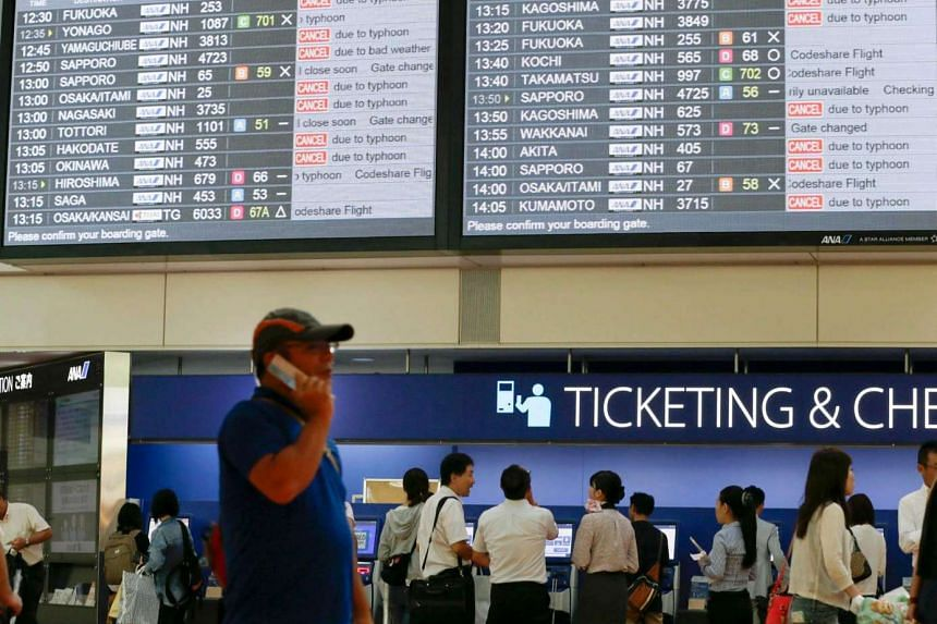 Passengers check domestic flight information on a monitor at Haneda Airport in Tokyo as over 450 domestic flights were cancelled.