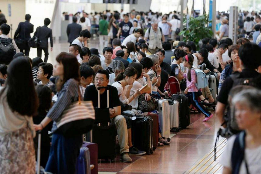 Passengers wait for flights to resume at Haneda Airport in Tokyo as over 450 domestic flights were cancelled.