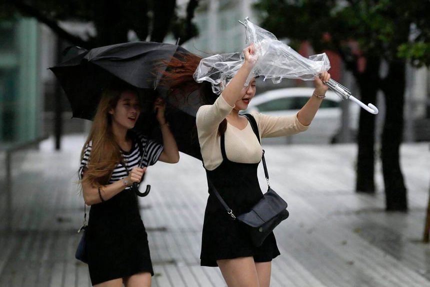 Pedestrians holding umbrellas struggle against strong winds and rain as Typhoon Mindulle hits eastern Japan.