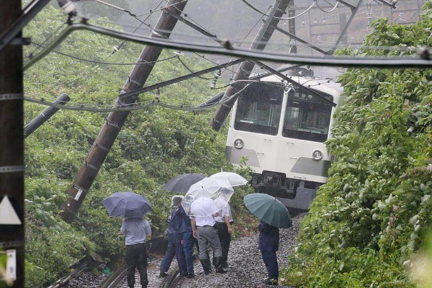 A derailed train in a landslide on the Seibu Tamako line in Higashimurayama, western Tokyo.