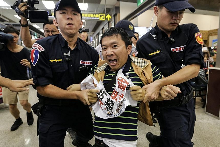 A member of the pro-independence Taiwan Solidarity Union shouting anti-China slogans while scuffling with the police at Songshan Airport in protest against the arrival of top Shanghai official Sha Hailin.