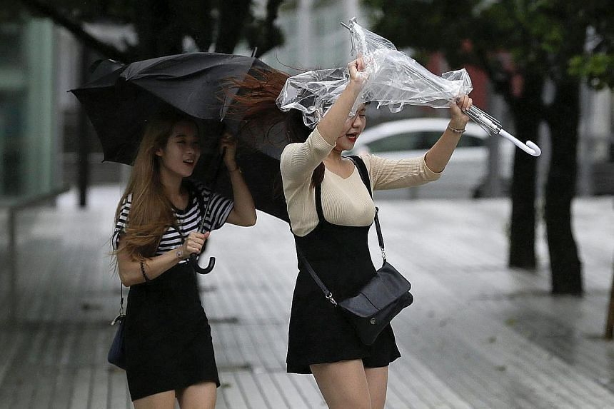 Pedestrians in Tokyo struggling against strong winds and rain when Typhoon Mindulle struck near the capital.