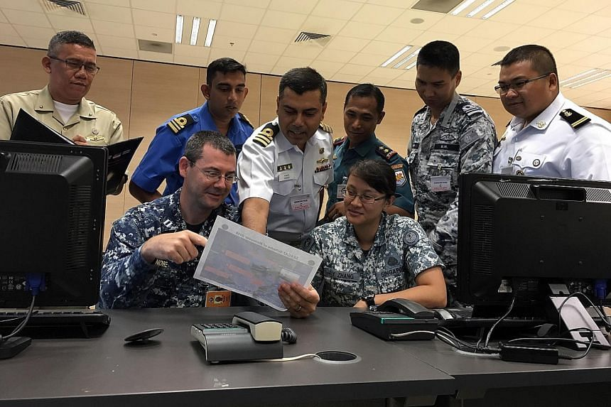 Seacat participants at the Multinational Operations and Exercises Centre at the Changi Command and Control Centre in Changi Naval Base. (Back row, from left) Lieutenant-Commander Alan Sonon of Philippines Navy; Lieutenant-Commander Nazrul Shaharin Os