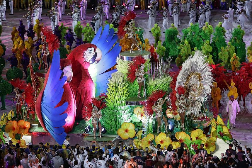 Left: A massive fireworks display capped off South America's first Olympics. Below left: Singapore's flag-bearer Griselda Khng snapping a selfie at the ceremony. Below: The show featured dance performances, elaborate costumes and light shows. Samba d
