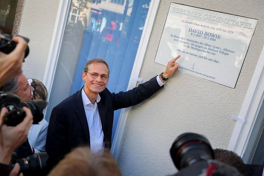 Mayor of Berlin Michael Mueller points at a commemorative plaque for David Bowie, on August 22.