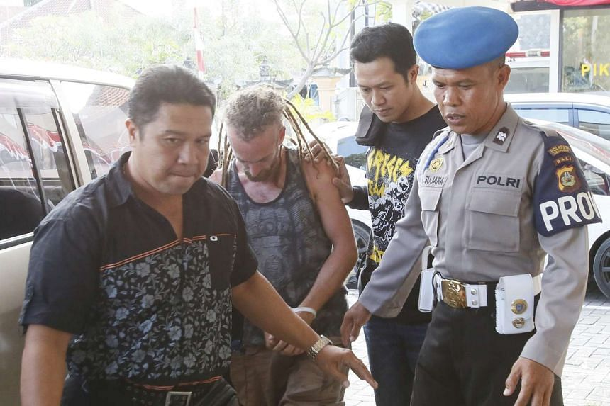 Indonesian police officers escorting Briton David Taylor (second from left), in Bali on Aug 20, 2016.