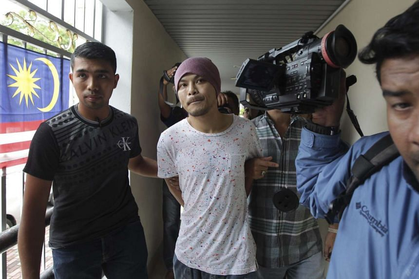 Malaysian singer Wee Meng Chee or Namewee (centre) is escorted by plaincloth policemen to the courthouse in Georgetown, Penang on Aug 22, 2016.