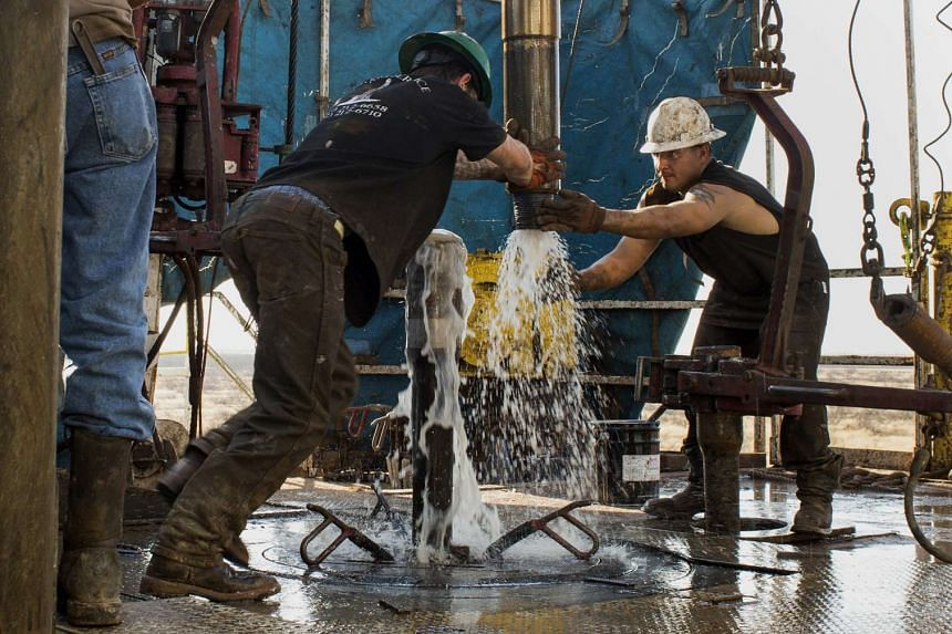 Workers extract natural petroleum in the Permian basin outside of Midland, Texas. Oil prices fell over 1% on Tuesday.