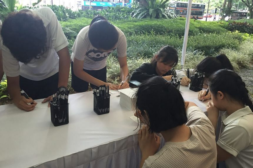 Students from the School of the Arts penning their tributes at the Istana.