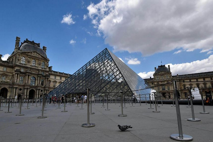 An empty waiting line in front of the Pyramid of the Louvre Museum on August 6.