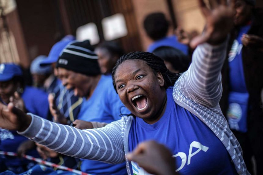 Members of South Africa's main opposition party Democratic Alliance members and supporters protest outside a courtroom in Pretoria.