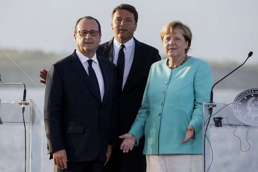 From left to right, Francois Hollande, Matteo Renzi, and Angela Merkel pose onboard the Italian aircraft-carrier on Monday (Aug. 22).