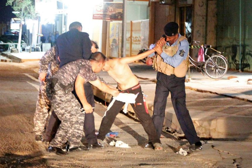 Iraqi security forces remove a suicide vest from a boy in Kirkuk, Iraq, on Sunday (Aug 21).
