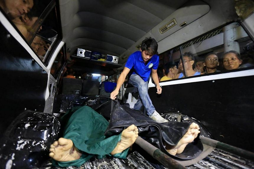 Filipino residents view dead bodies of alleged drug dealers killed during a police operation against illegal drugs in Manila.