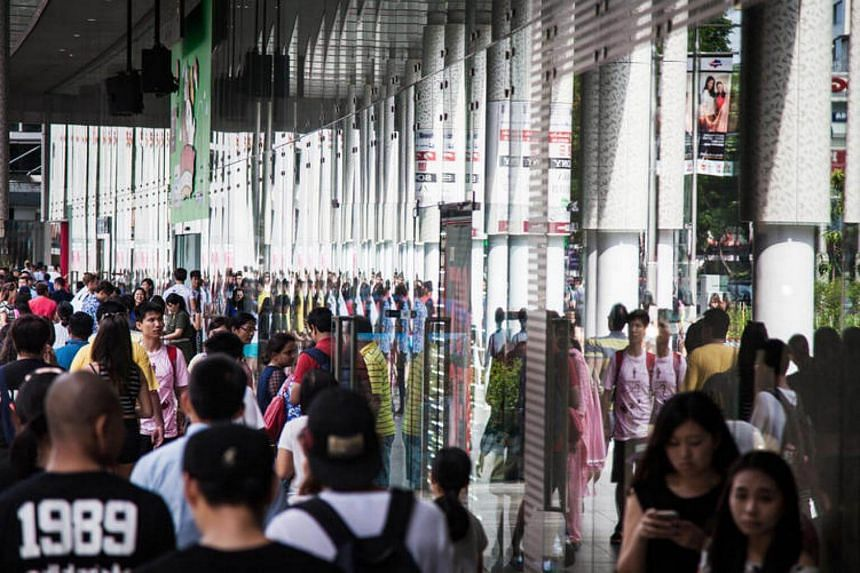 Shoppers and pedestrians walk along Orchard Road. The consumer price index fell again in July - the 21st straight month of decline.