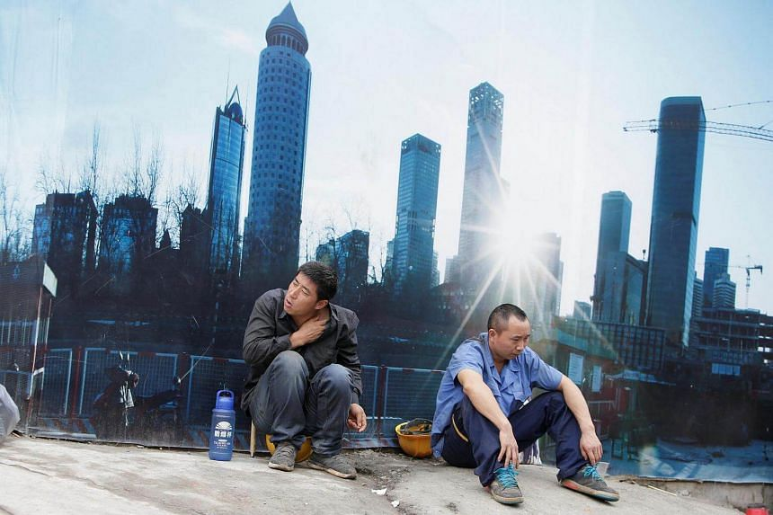 Workers rest outside a construction site in Beijing's central business district. China's state construction giants are set to merge.