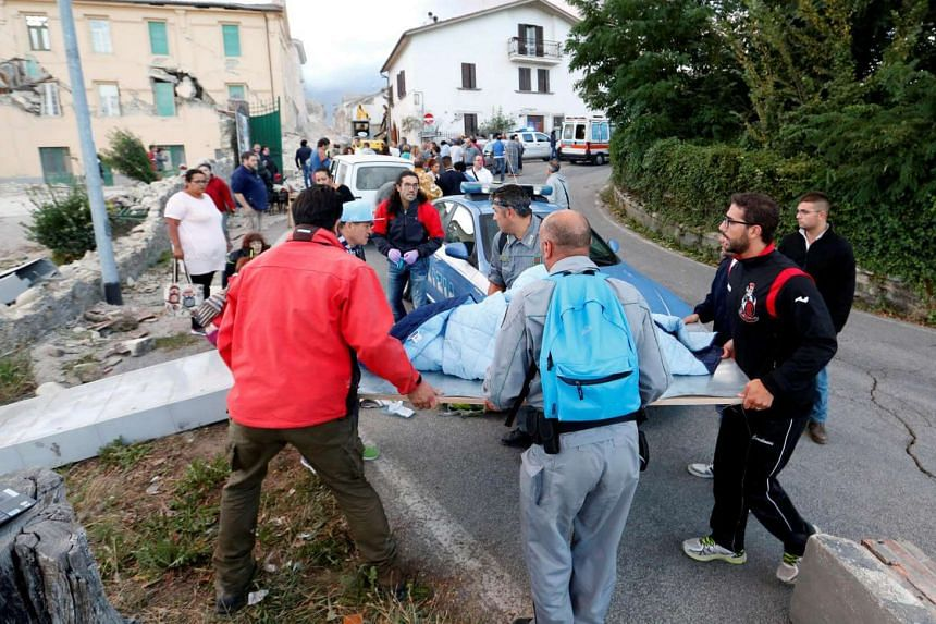 People stand along the road following a quake in Amatrice, central Italy, on Aug 24.