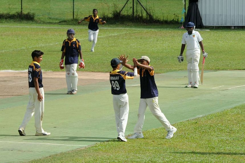 ACS (I) players high-fiving each other during the C Division cricket final against RI.