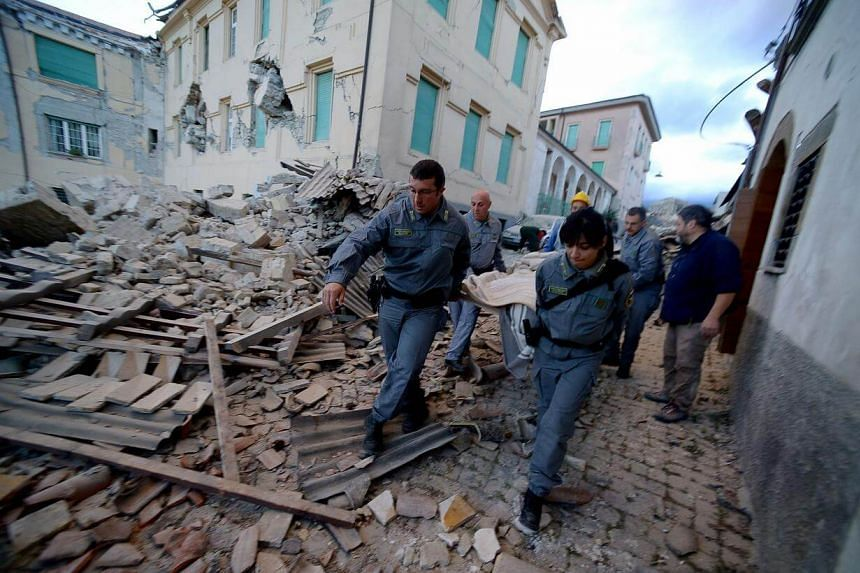 Rescuers carry a man from the rubble after a strong heartquake hit Amatrice on Aug 24.