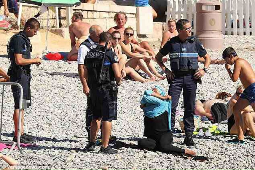 One of the viral photos showing a woman removing her tunic while surrounded by police on a beach in Nice.