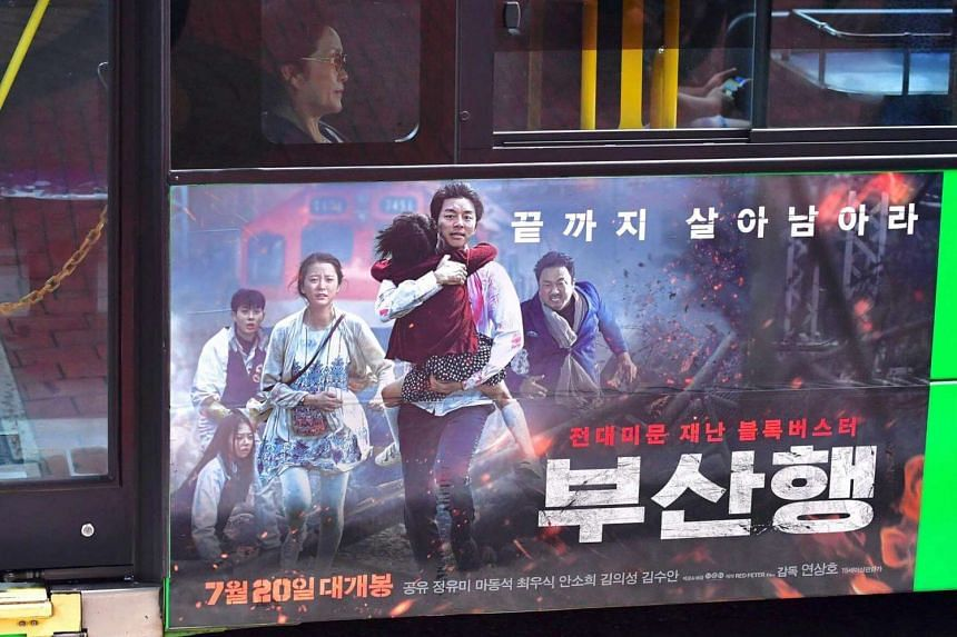 """A woman sits on a bus which carries a poster of the first South Korean zombie blockbuster, entitled """"Train to Busan"""", in Seoul on August 4."""