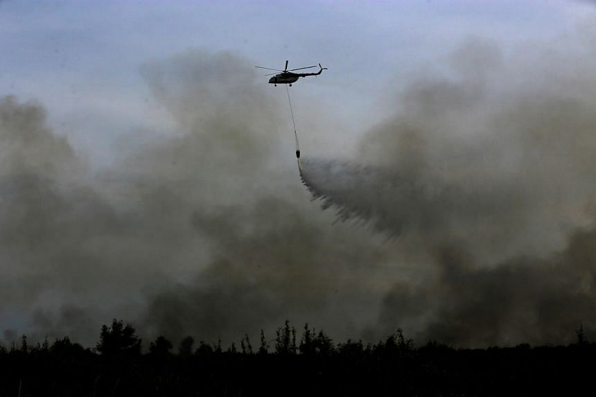 A helicopter from the Indonesian National Disaster Management agency drops water on a fire in Ogan Ilir, near Palembang, South Sumatra, Indonesia on August 11.